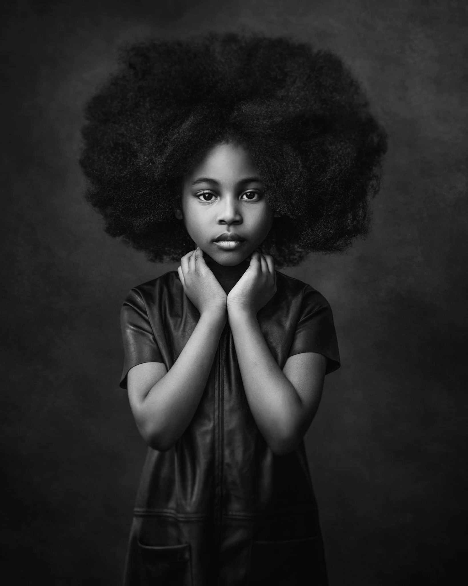 Afro American girl wearing black leather dress posing with hands around her neck for a fine art portrait