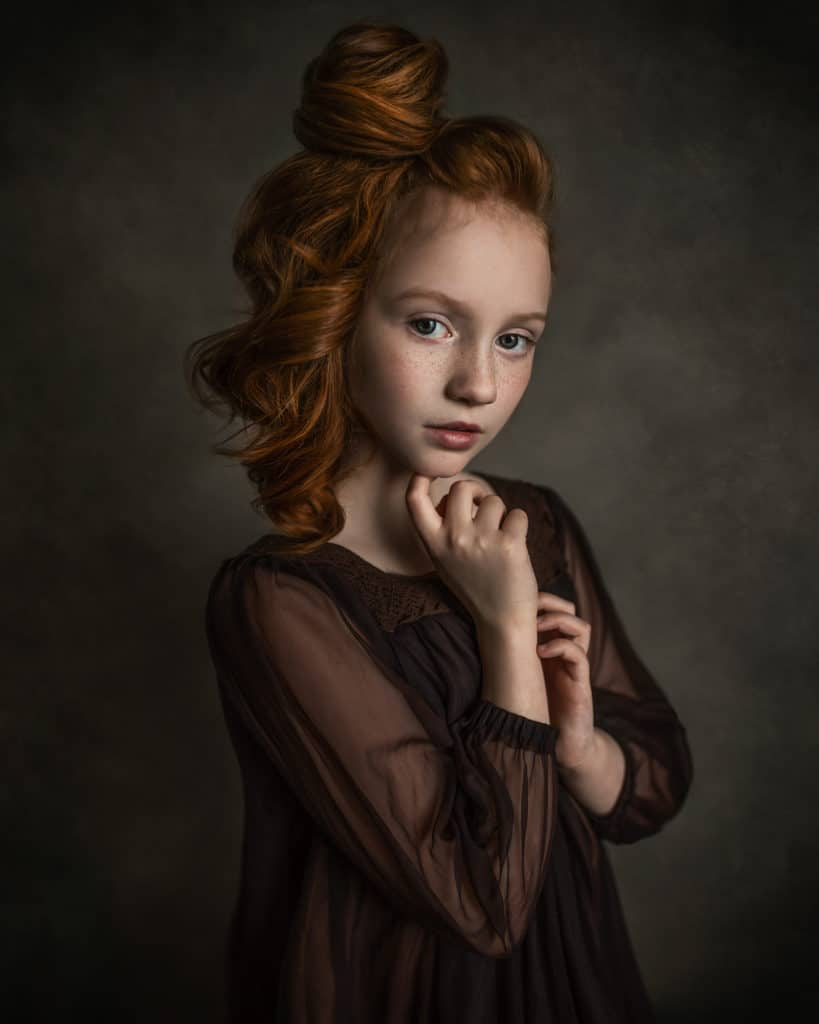 Loop lighting technique used to create the image of young red hair girl wearing the brown dress