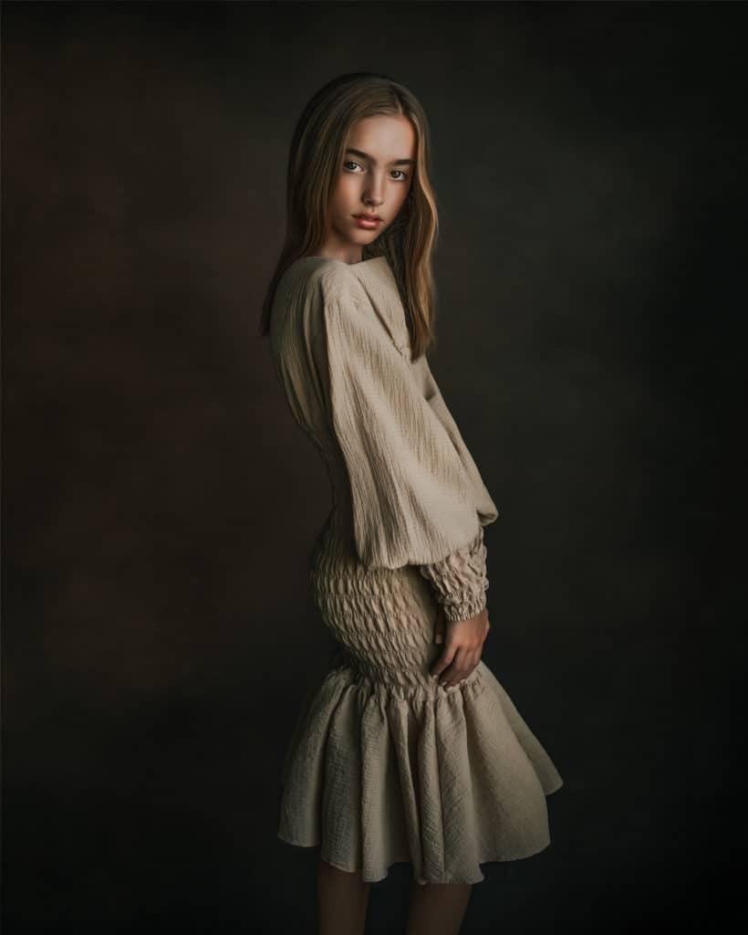 young girl wearing creamy dress posing next to the window