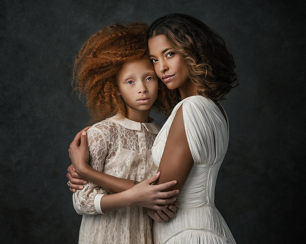 mother holding tightly her teenage daughter in creamy lace dress during their photoshootr