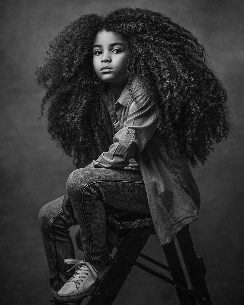 black and white fine art portrait of a boy with long curly hair