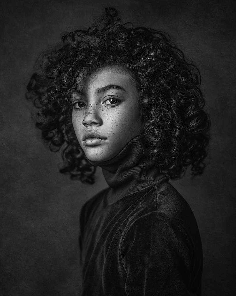 African American teenage boy with curly black hair and freckles wearing black velvet high neck top