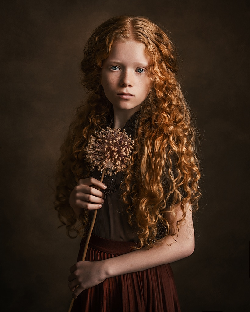 girl with freckles and long, curly, ginger hair holding a dry flower wearing vintage brown clothes