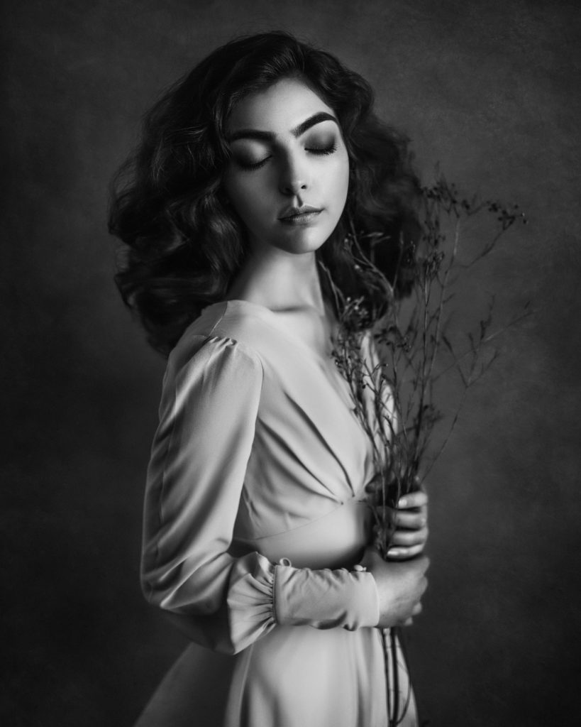 split lighting created with window light visible on the face of beautiful model holding dry flowers