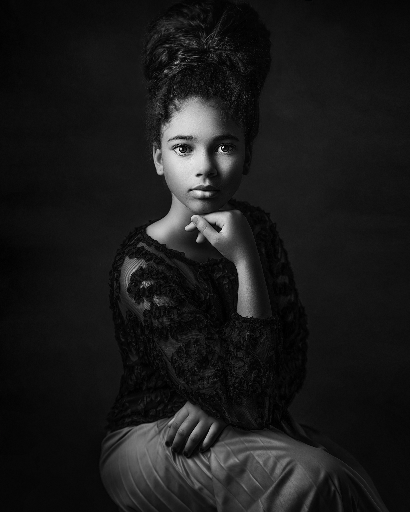 black and white portrait of Afro American girl sitting on a chair created with Rembrandt studio light set up