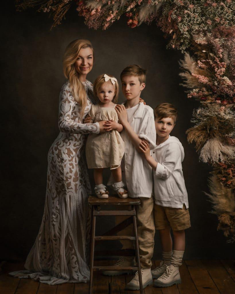 boho style family photoshoot, mom and kids wearing white boho clothing, flower arch